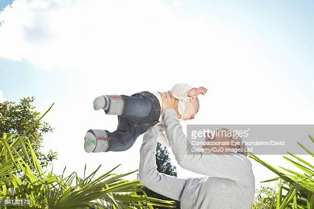 "mother lifting baby - ""compassionate eye"" fotografías e imágenes de stock"