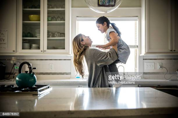 Mother lifting daughter (7yrs) in kitchen