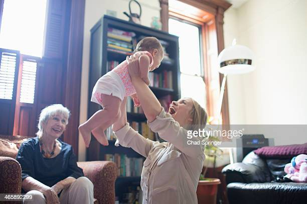 Mother lifting daughter with grandmother watching