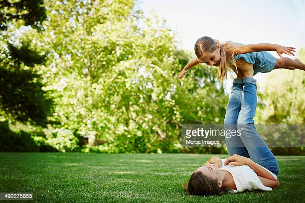 mother lifting daughter with legs in park - lying down foto e immagini stock