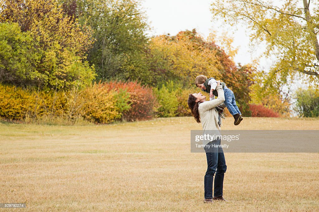 Mother lifting his son (4-5) up in air : Stock Photo