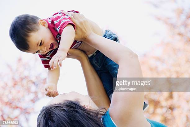 Mother lifting son into air