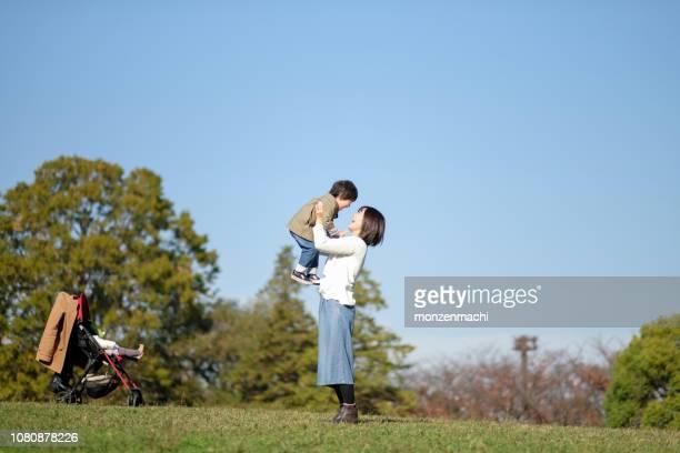 母リフティング幼児公園 - embracing ストックフォトと画像