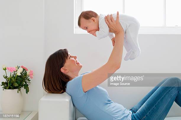 Mother lifting up baby girl