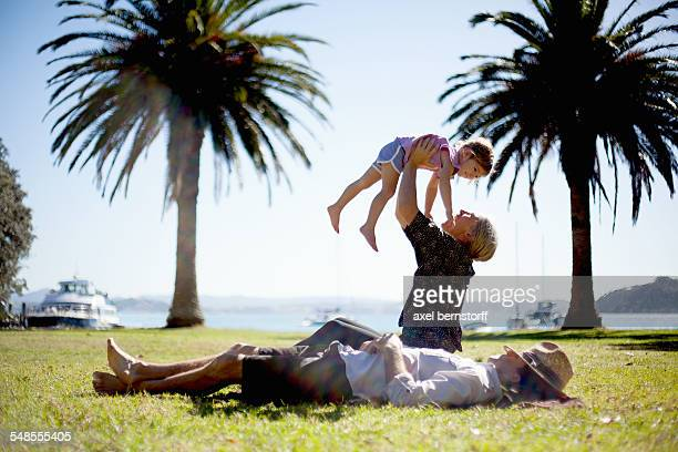 Mother lifting up daughter in park, New Zealand