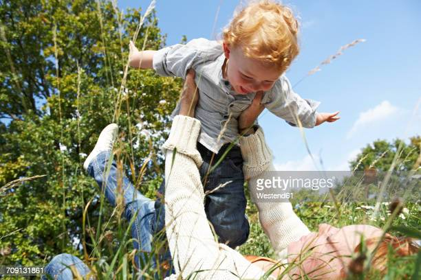 Mother lifting up happy son in meadow