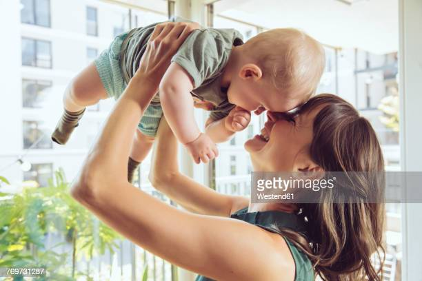 Mother lifting up her baby at home