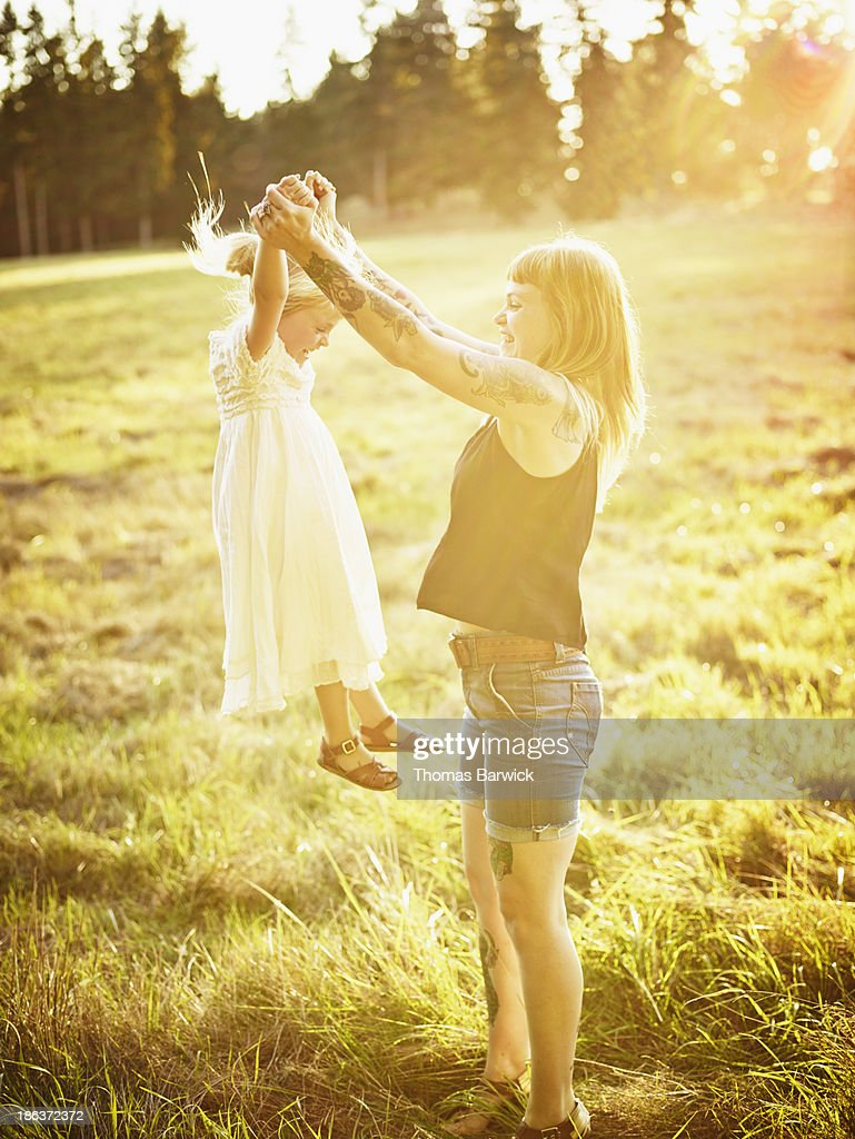Mother lifting young daughter in air by arms : Stock Photo