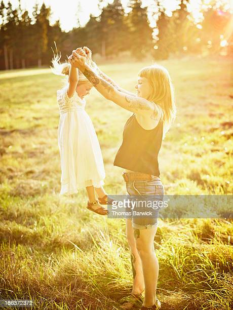 Mother lifting young daughter in air by arms