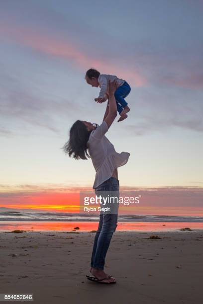 mother lifts her baby girl up in the air at a beach. - seascape stock pictures, royalty-free photos & images