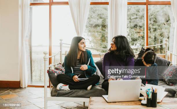 a mother listens to her teenage daughter intently during a homeschooling session - child stock pictures, royalty-free photos & images