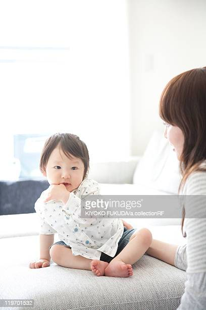 Mother Lookign at Baby Boy Sitting on Sofa