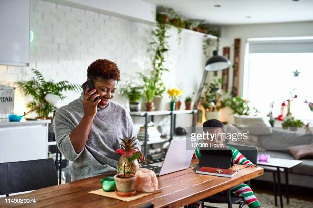 mother looking after son and working from home - working from home stock pictures, royalty-free photos & images