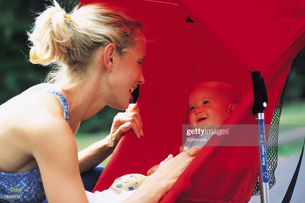 Mother looking at baby in stroller : Stockfoto
