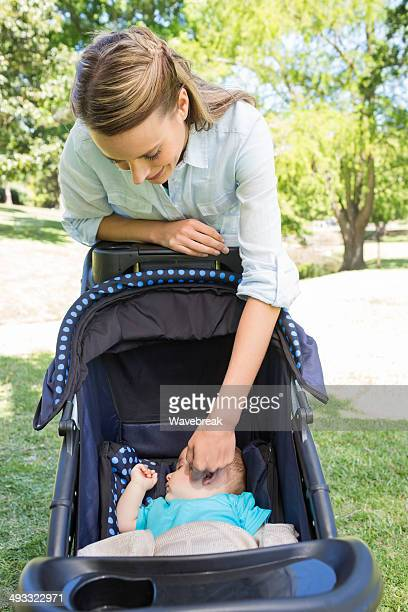 Mother looking at baby sleeping in pram