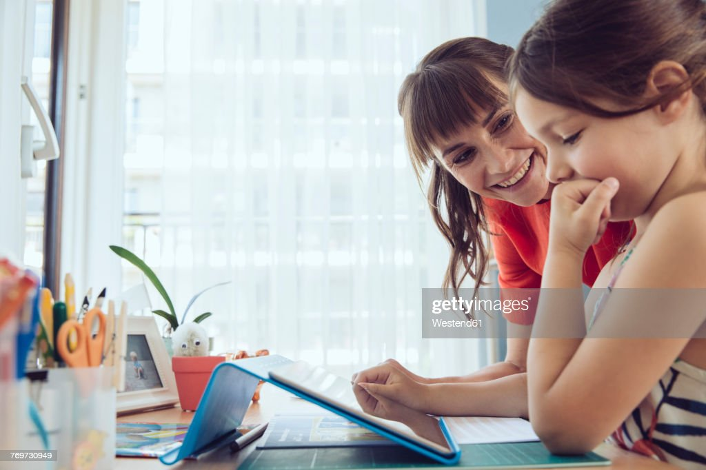 Mother looking at daughter using tablet at home : Stock-Foto