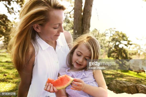 Mother looking at girl holding watermelon in backyard