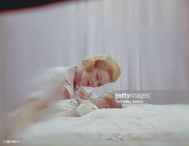 Mother looking at her baby boy in bedroom