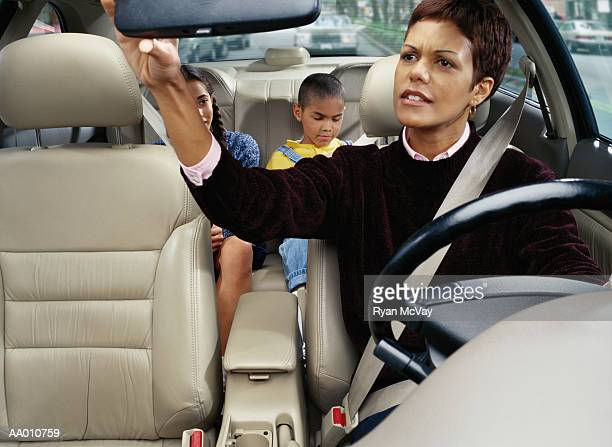 mother looking at her children in the back seat - family inside car stock photos and pictures