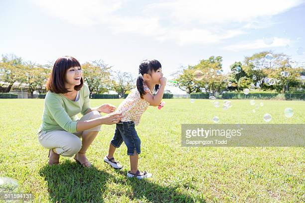 Mother Looking At Her Daughter Blowing Bubbles