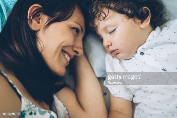 mutter, die ihr kleinkind schlafen betrachten - sohn stock-fotos und bilder