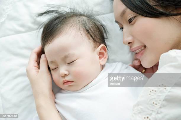 Mother looking at sleeping baby girl