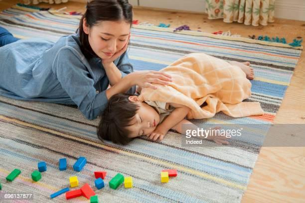 mother looking at sleeping boy on carpet - 昼寝 ストックフォトと画像