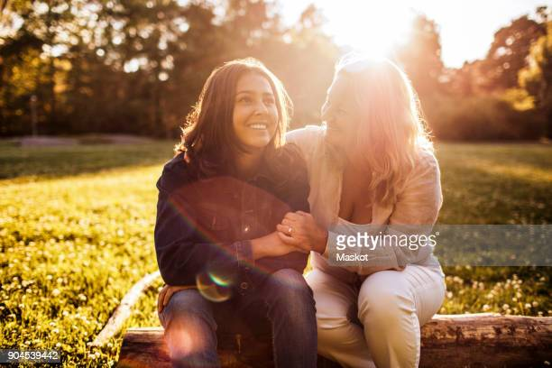 Mother looking at smiling daughter while sitting on log at park during sunny day
