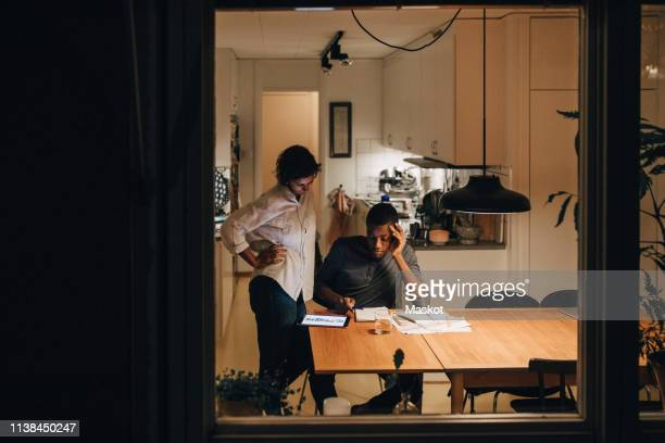 mother looking at son studying while sitting in living room seen through window - home schooling stock pictures, royalty-free photos & images