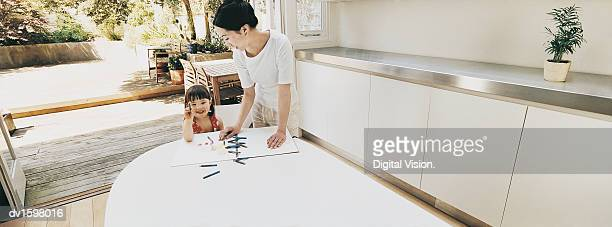 Mother Looking Down at Her Daughter Colouring In a Colouring Book on a Kitchen Table