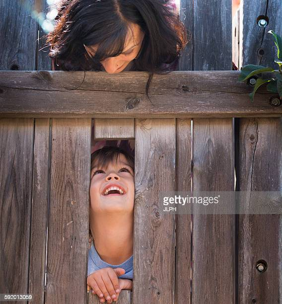 Mother looking over at son, through hole in fence