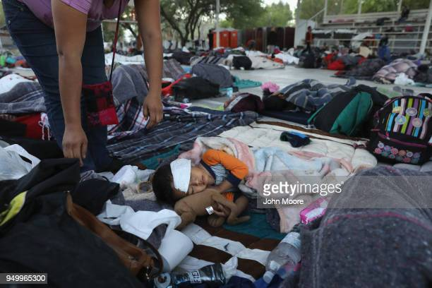 A mother looks over her son after a night's rest on an outdoor basketball court during a rest stop on their journey towards the USMexico border on...
