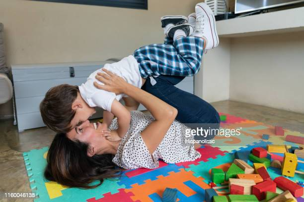 mother lying down on floor while carrying toddler very playfully and smiling - hispanolistic stock photos and pictures