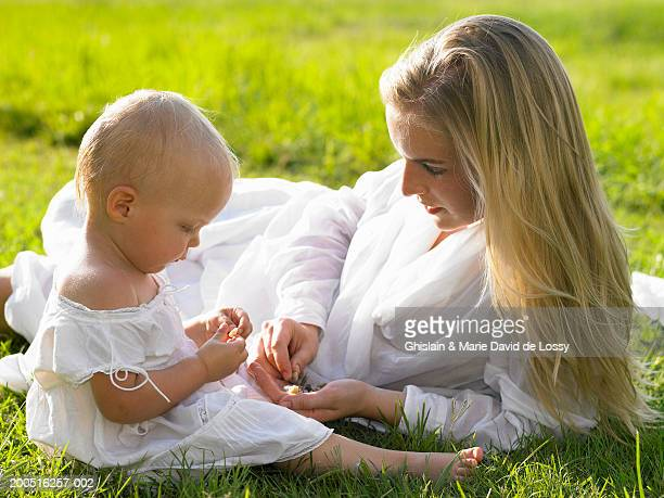 mother lying in grass with baby girl (18-21 months) - 18 23 months stock pictures, royalty-free photos & images