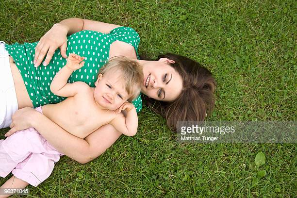 Mother lying on a meadow with her Baby facing the
