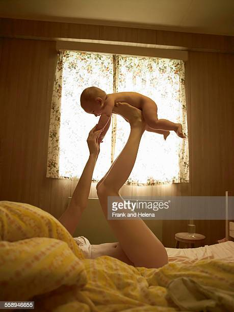 Mother lying on bed balancing baby son on feet