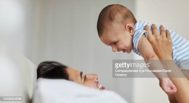 Mother lying on bed holding baby boy overhead
