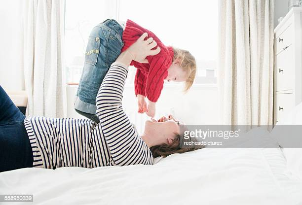 mother lying on bed lifting son above head - overhemd en stropdas stock pictures, royalty-free photos & images