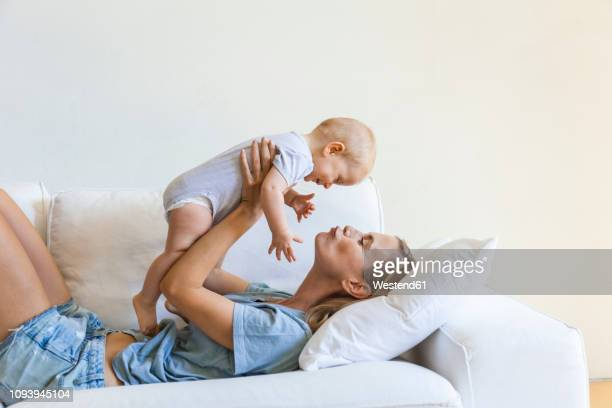 mother lying on couch holding her baby girl - mother stock-fotos und bilder