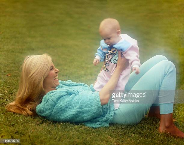 Mother lying on grass holding baby