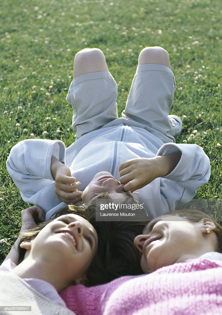 Mother lying on grass with boy and girl, head to head : Stockfoto