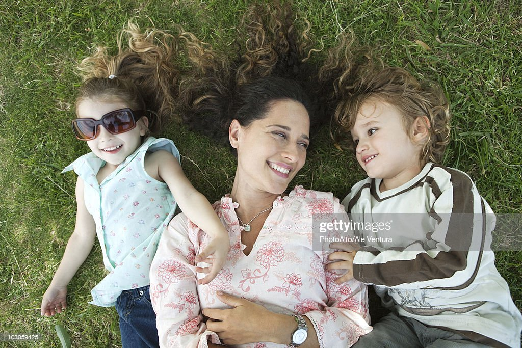 Mother lying on grass with young children : Stock Photo