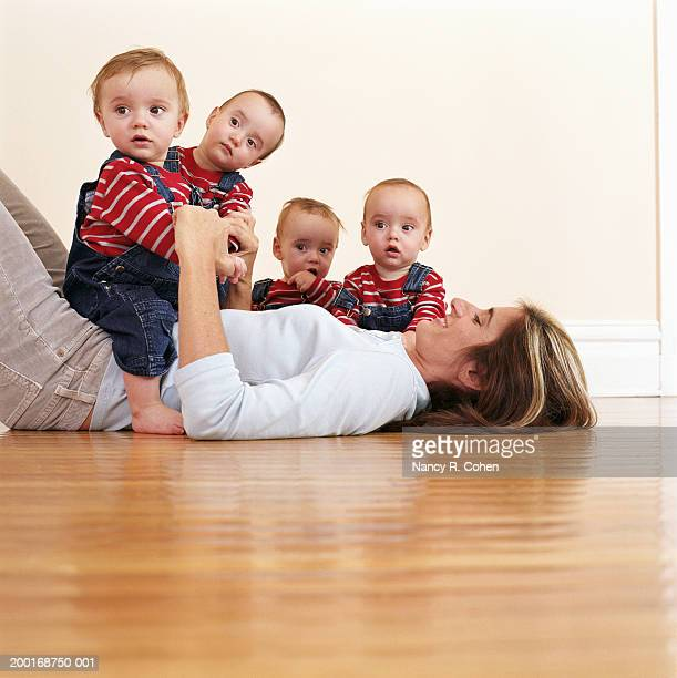 Mother lying on hardwood floor with quadruplet babies (9-12 months)