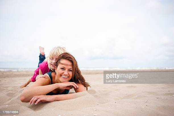 Mother lying on the beach with her daughter on top