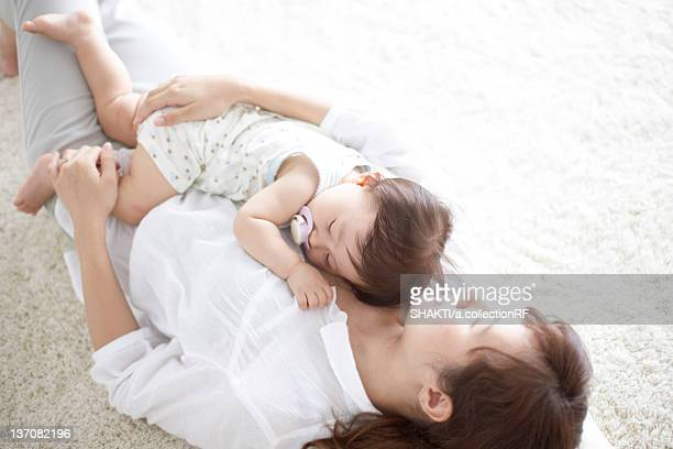 Mother lying on the floor and embracing baby