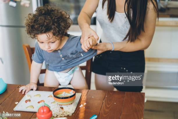 mother make the mess after toddler lunch - imperfection stock pictures, royalty-free photos & images