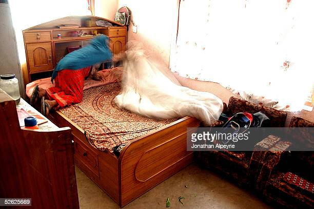 A mother makes a bed inside the children's room March 3 2005 in the Kathmandu Valley village of Mulpan Nepal The children are getting ready to go to...