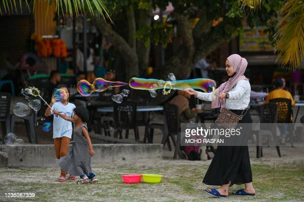 Mother makes bubbles to attract her children at Pantai Cenang in Langkawi on September 15 a day before the Malaysian holiday island is set to reopen...