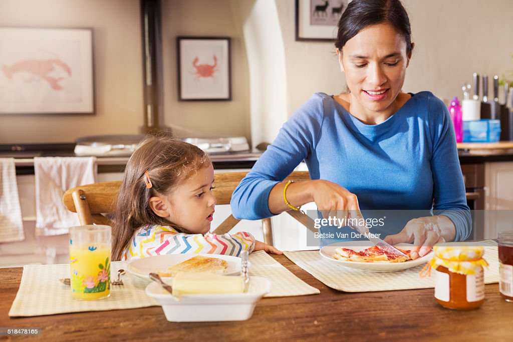 Mother makes sandwich for daughter in kitchen. : Stock Photo