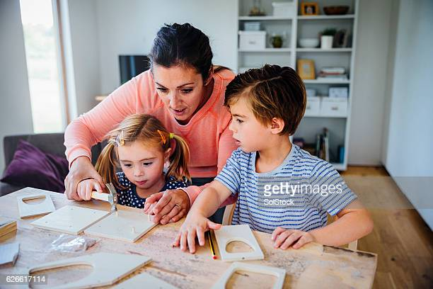 Mother Making a Bird Box with her Children